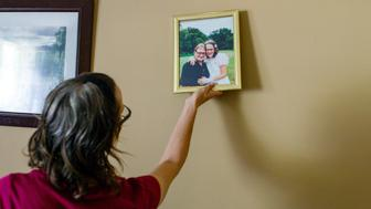 Meredith takes a framed photo of her and her husband, Jay, on their wedding day.Meredith Lawrence's husband, Jay Lawrence, committed suicide after his pain medication prescription was severely restricted after a strict crackdown on prescription opioids.