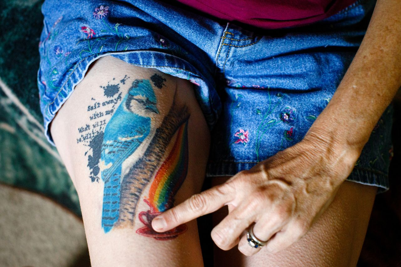 """Meredith Lawrence shows the tattoo she got after her husband'€™s death. The bluejay represents her husband, Jay; a cup of coffee is the way she loves to start her day; and the quote is """"Sail away with me, what will be will be."""""""