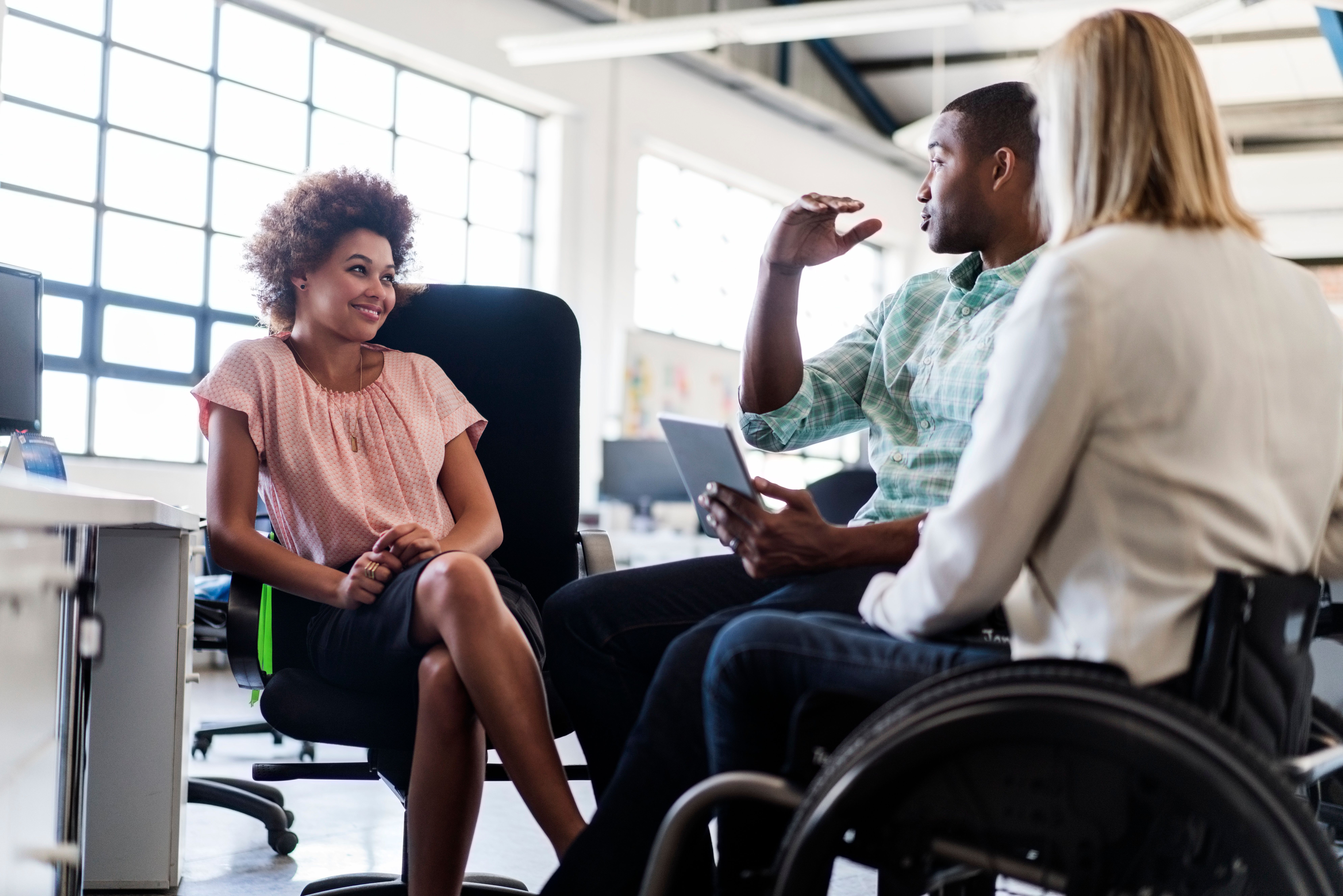 Businessman discussing with female colleagues in office. Disabled businesswoman is sitting in wheelchair with executives at brightly lit workplace. They are in smart casuals.