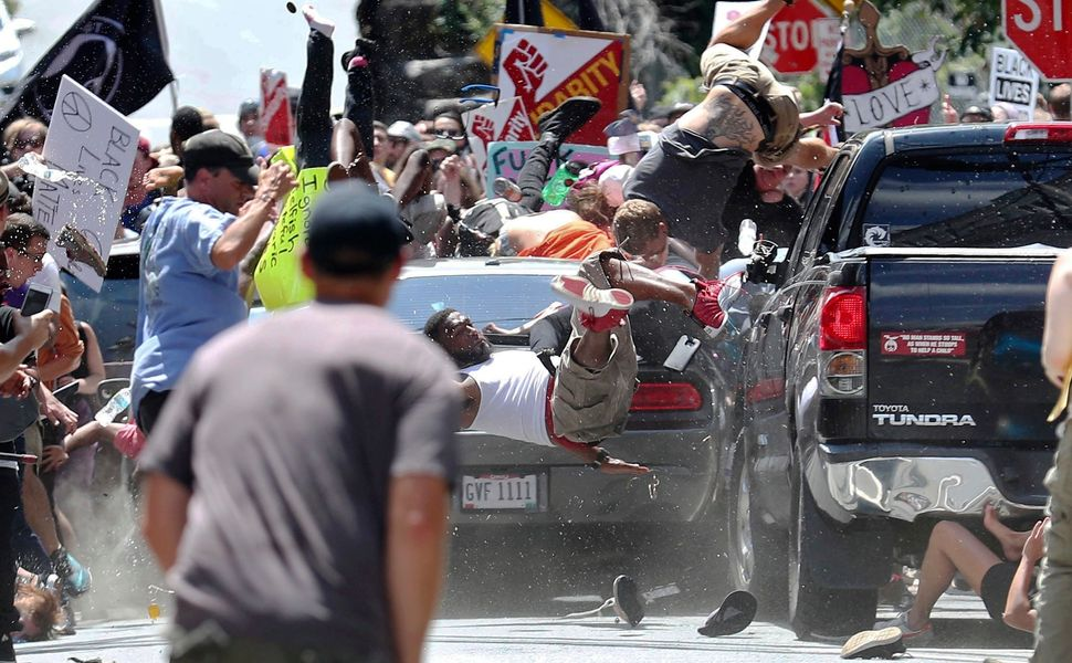 People fly into the air as a vehicle drives into a group of protesters in Charlottesville on Aug. 12, 2017.