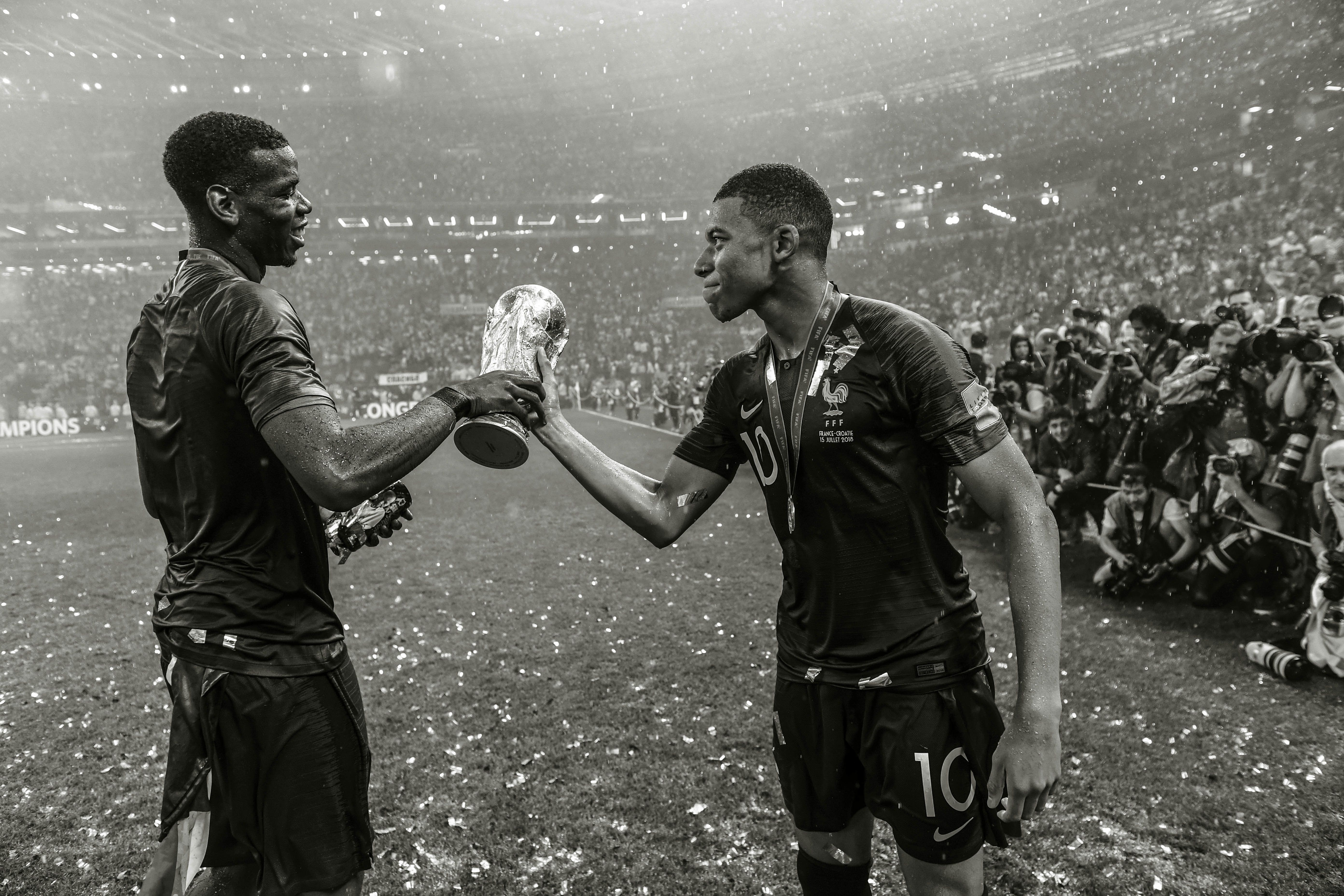 MOSCOW, RUSSIA - JULY 15:  (EDITORS NOTE: This image has been converted to black and white) Paul Pogba (L) and Kylian Mbappe of France celebrate victory with the World Cup Trophy following his side victory in the 2018 FIFA World Cup Russia Final between France and Croatia at Luzhniki Stadium on July 15, 2018 in Moscow, Russia.  (Photo by David Ramos - FIFA/FIFA via Getty Images)