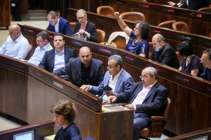 Israeli-Arab Member of Parliament Ahmed Tibi (front row, right) with fellow deputies at the Knesset Plenary Hall session ahea