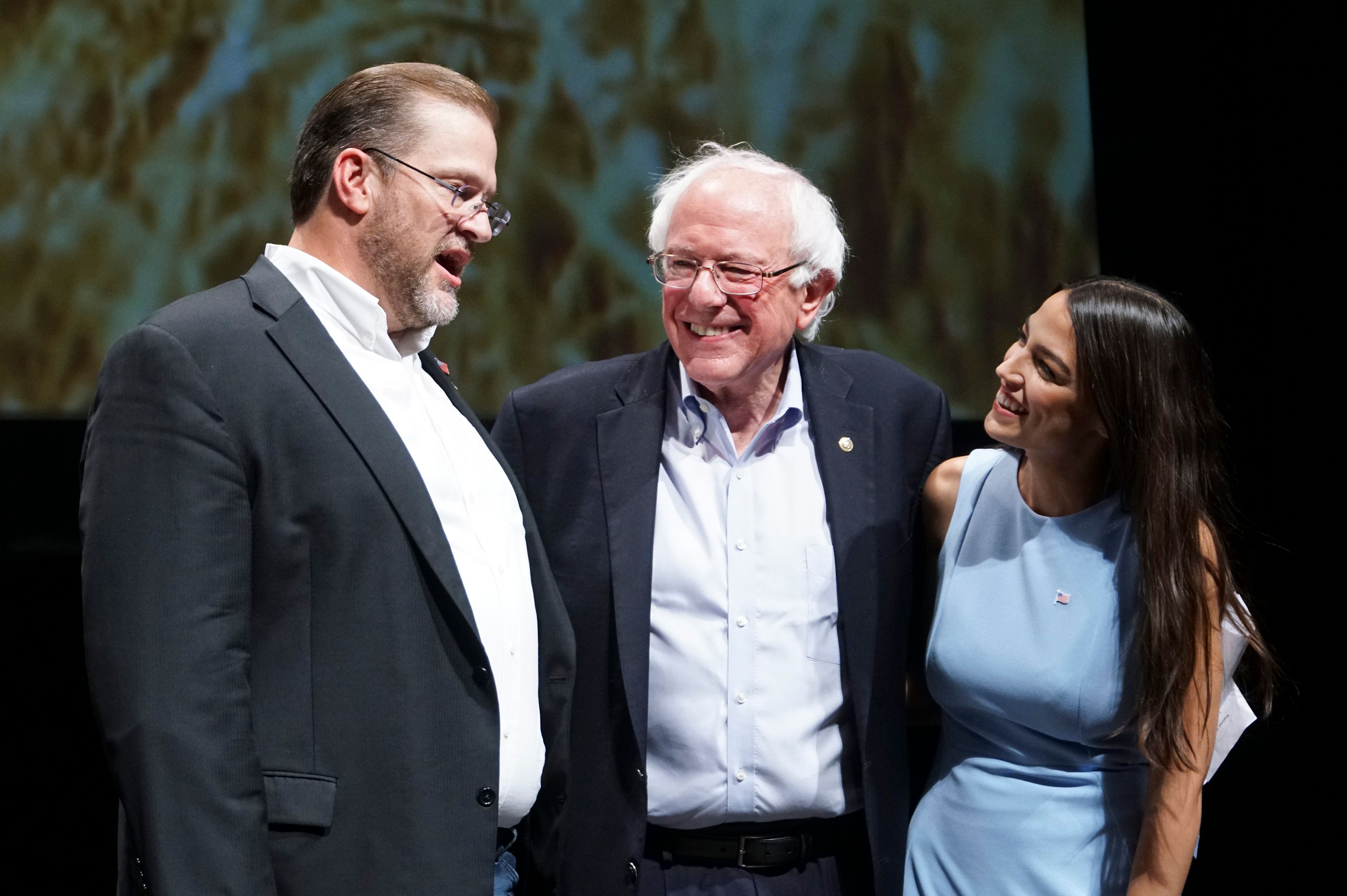 Kansas congressional candidate James Thompson left US Sen Bernie Sanders I-Vt and Alexandria Ocasio-Cortez a Democratic congressional candidate from New York stand together on stage after a rally Friday July 20 2018 in Wichita Kan Jaime Green/The Wichita Eagle via AP