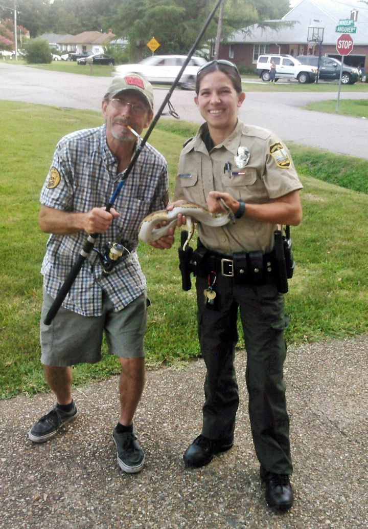 Kenny Spruill and an unidentified animal control officer pose with the female ball python. The reptile, a lost pet, was later