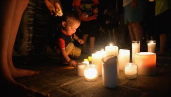 BRANSON, MO - JULY 20: A child places a candle down during a evening candlelight prayer vigil at Life Christian Center Church on July 20, 2018 in Branson, Missouri. Hundreds of Branson and surrounding areas are gathering to pay their respects to the victims after a duck boat capsized in Table Rock Lake during a thunderstorm on Thursday. (Photo by Michael Thomas/Getty Images)