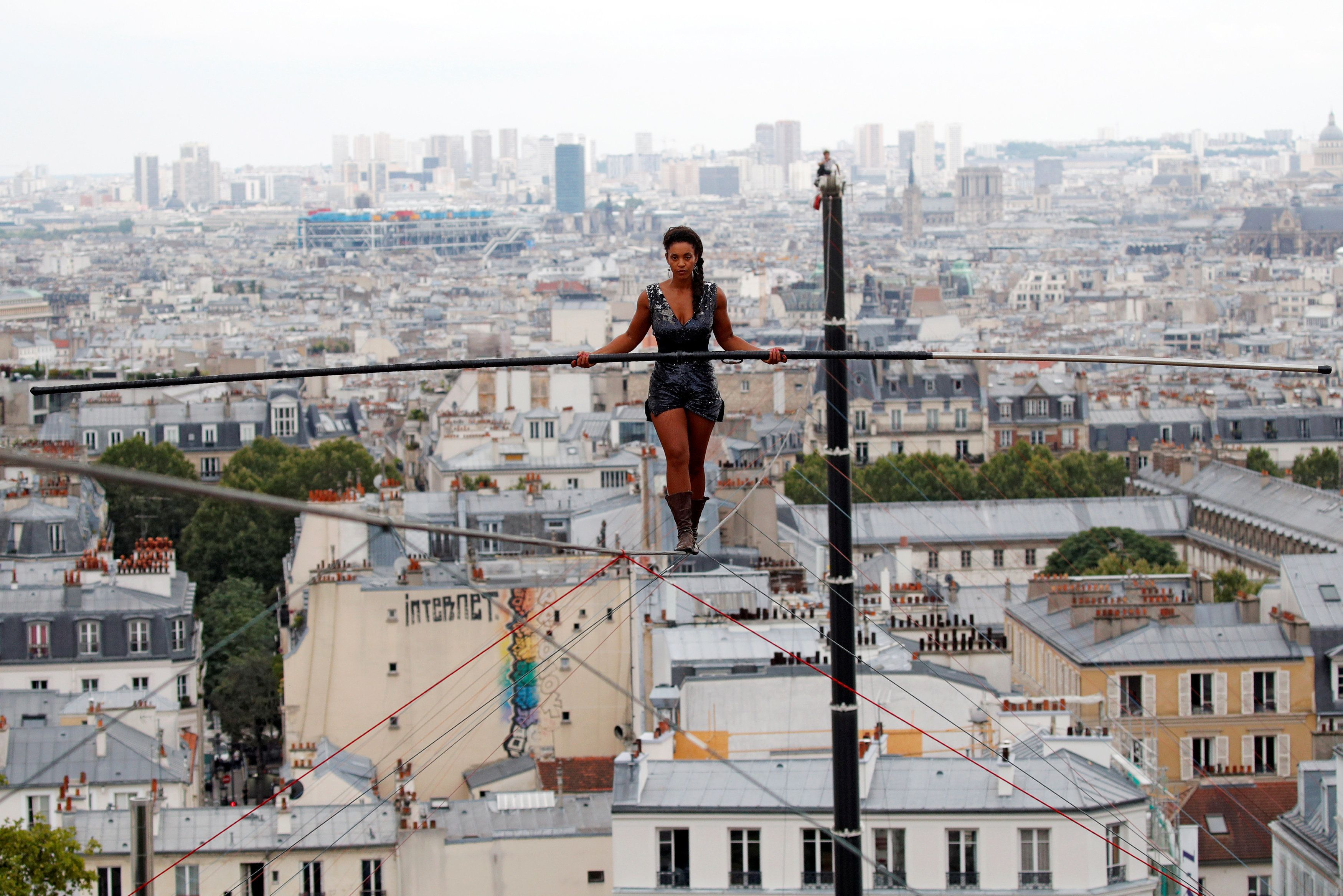 Tightrope walker Tatian-Mosio Bongonga advances on a tightrope as she scales the Monmartre hill towards the Sacre Coeur Basilica (not pictured) in Paris, France, July 20, 2018.   REUTERS/Philippe Wojazer