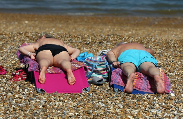 A couple enjoy the warm weather on the beach in Whitstable, Kent, as the hot weather