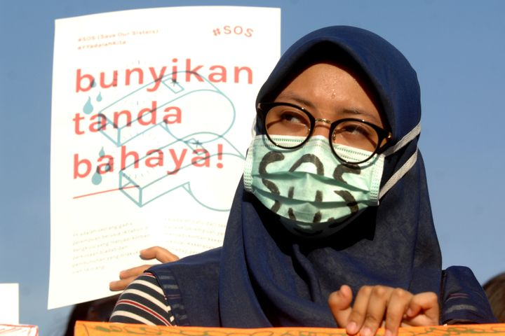 """Women Action Committee during the protest against sexual violence in Indonesia, with the slogan """"SOS,"""" Save Our Sisters, in J"""