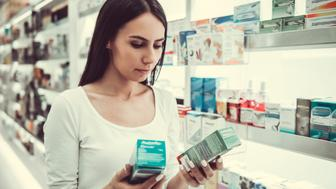Beautiful young woman is choosing a medication at the pharmacy