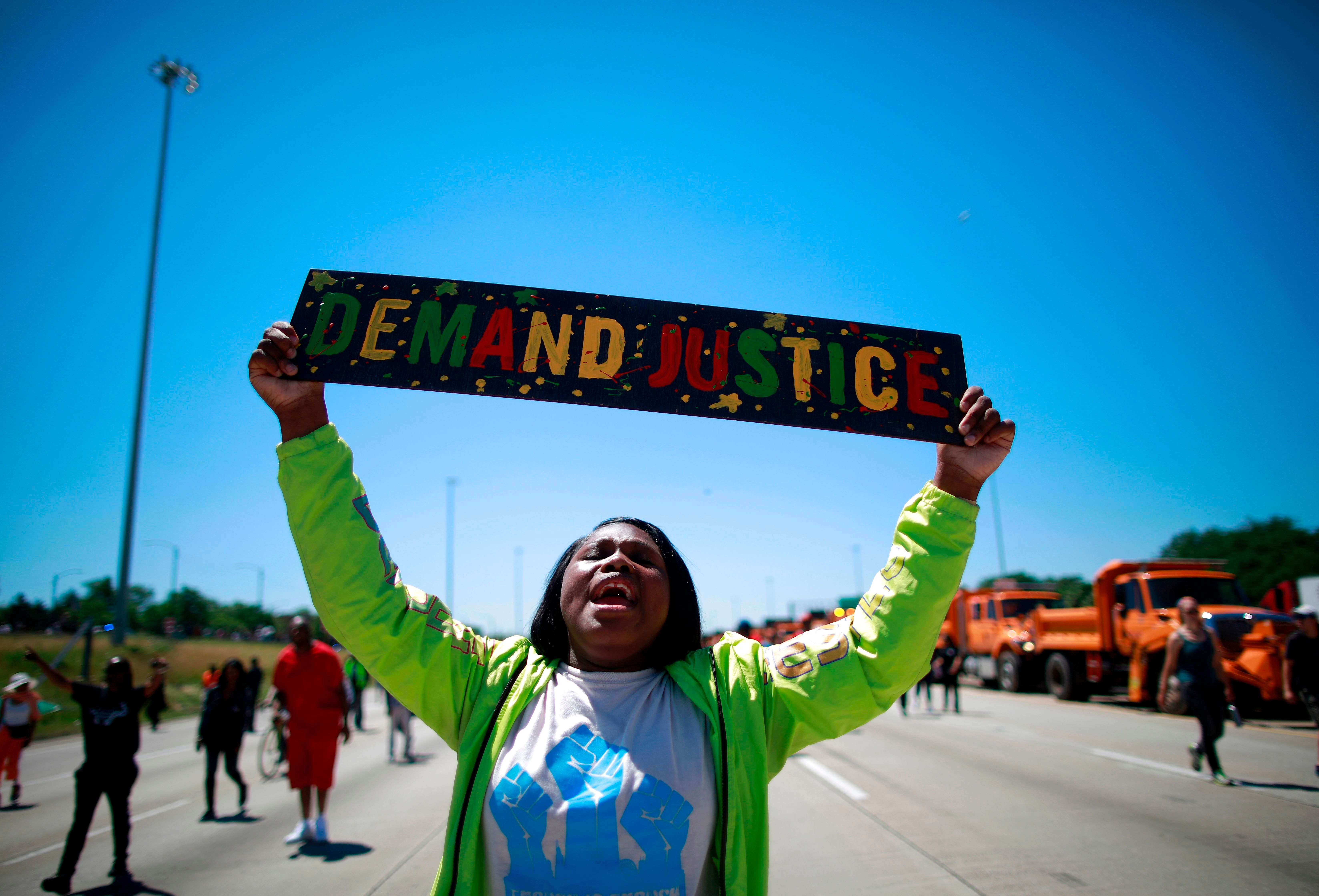 TOPSHOT - A protestor marches along the shutdown Dan Ryan Expressway during an anti-violence demonstration in Chicago, July 7, 2018. - Thousands of protesters against Chicago's pervasive gun violence partially shut down a major expressway in the third-largest US city, which leads the country in murders.  The demonstrators, led by a local pastor known for decades of anti-violence advocacy in Chicago's hard-scrabble South Side, completely closed off one side of the Dan Ryan Expressway for about an hour. (Photo by JIM YOUNG / AFP)        (Photo credit should read JIM YOUNG/AFP/Getty Images)