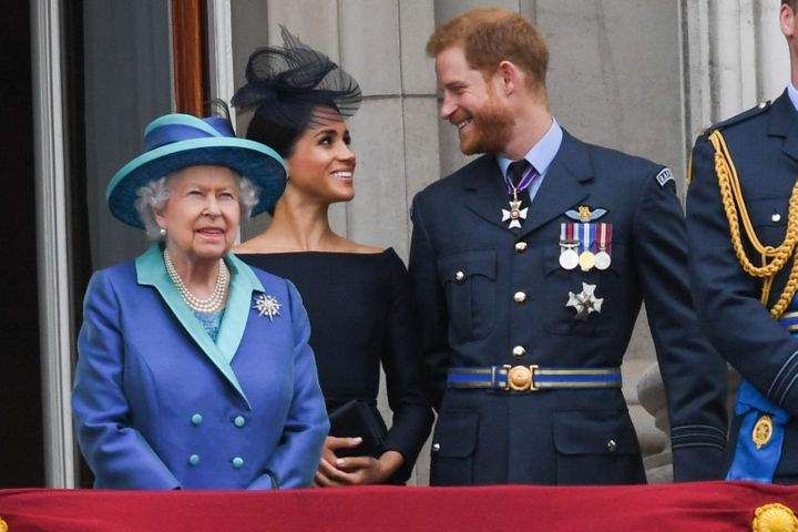 Queen Elizabeth ll, Meghan, Duchess of Sussex and Prince Harry, Duke of Sussex stand on the balcony of Buckingham Palace to m