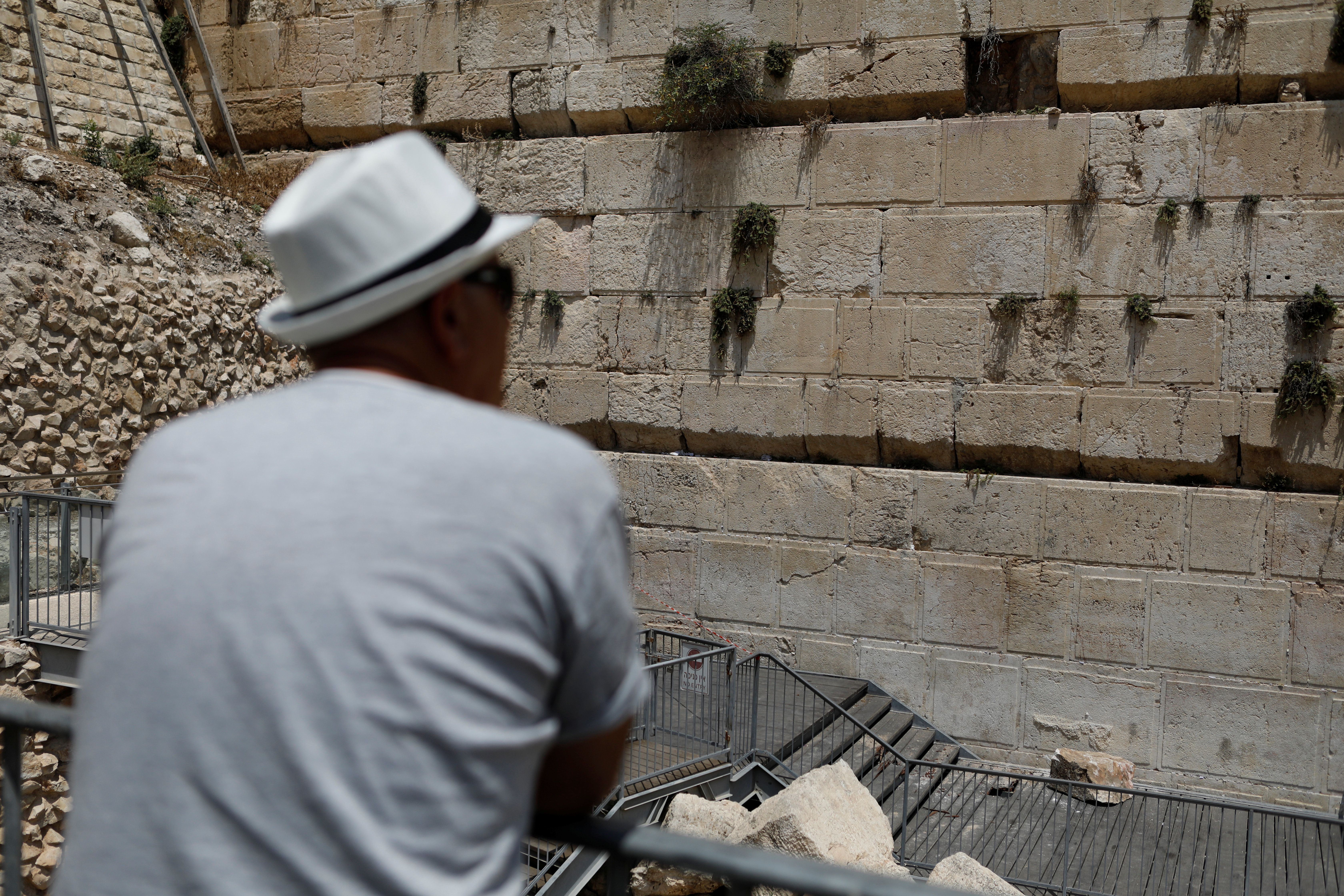 A man looks at the stone that fellfrom the Western Wall on Monday.
