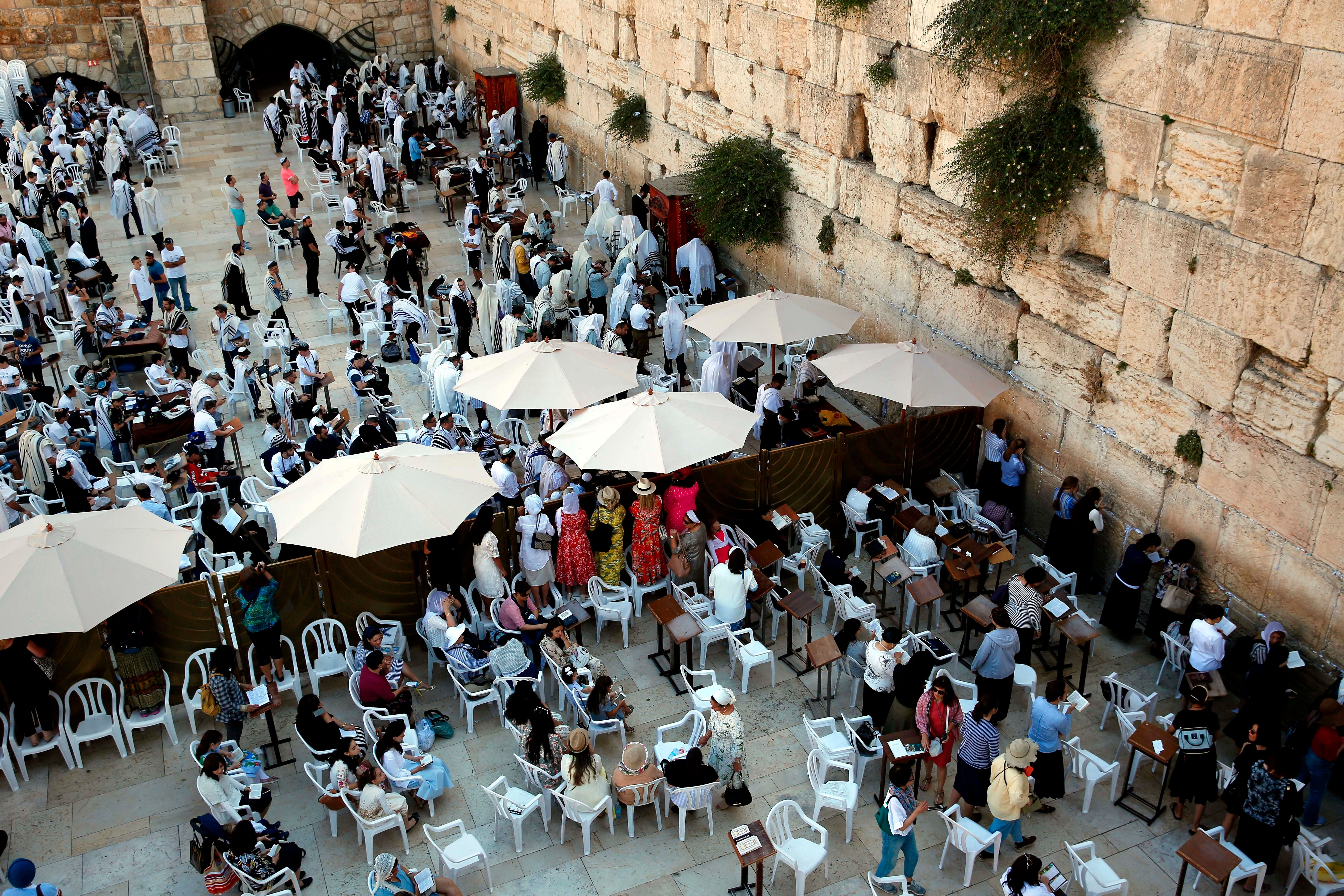 Jewish women pray at the women's section, on the right, which is separated from the men's section of the Western Wall.