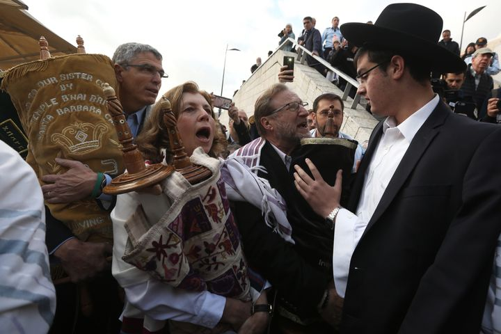 An ultra-Orthodox Jewish man tries to prevent Anat Hoffman (center), the founder of Women of the Wall, from entering the wome