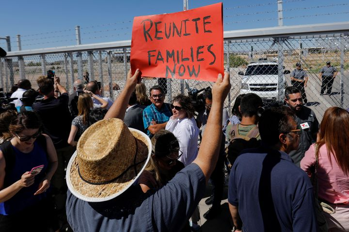 A protester holds up a sign as mayors from U.S. cities are stopped from entering the children's tent encampment in Tornillo,