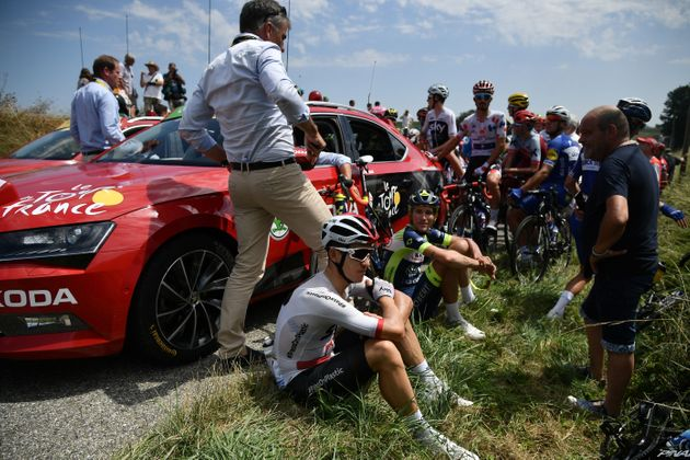 Riders sit after General Director of the Tour de France, France's Christian Prudhomme (Rear L) halted...
