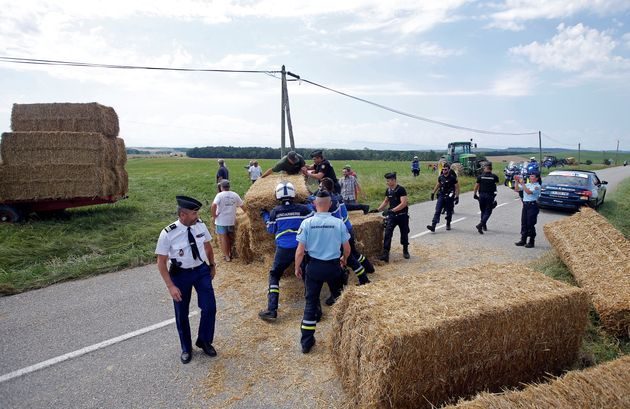 Police officers remove hay bales off the road after a