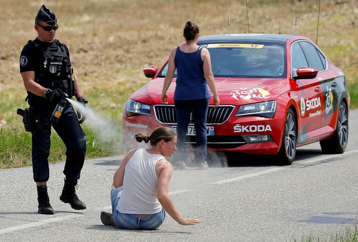 A police officer pepper-sprays a protester as another protester stands in front of the race director's car. The farmers were