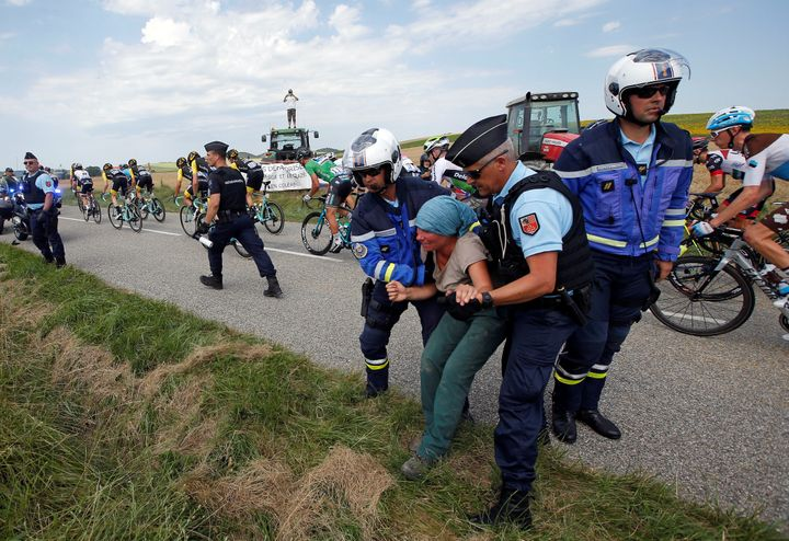Police officers carry a protester off the road on Tuesday as cyclists with the Tour de France pass.