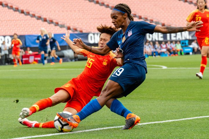 Lou Jiahui (left) of China battles with Crystal Dunn of the U.S. in Cleveland on June 12, 2018. Compared with male players, female players get paid less and have fewer resources.