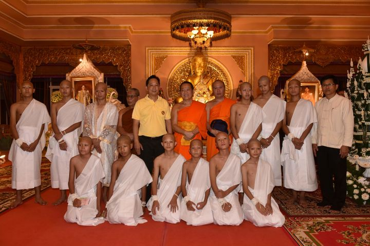 Eleven members of the Wild Boars soccer team and their coach wear white robes  at a Buddhist te
