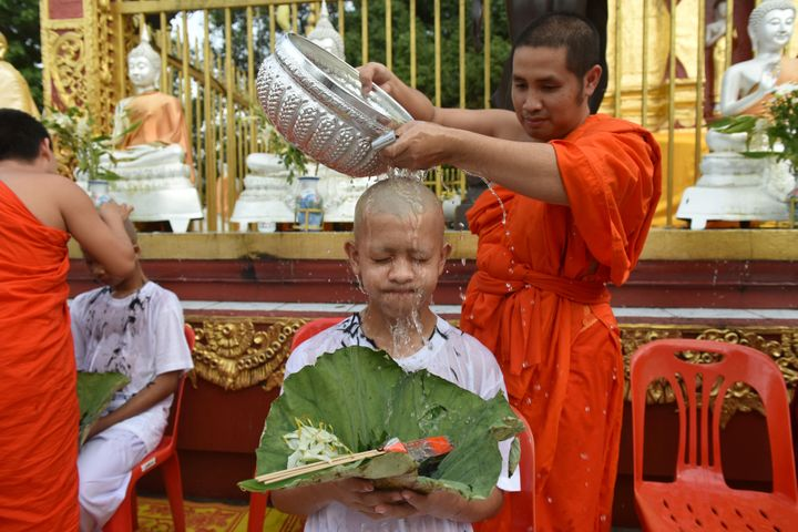 A Buddhist monk bathes the shaved head of a rescued Thai boy on Tuesday.