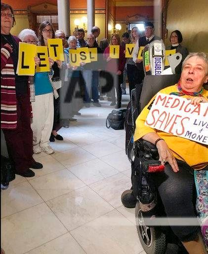 Activists, urging Connecticut state legislative leaders not to cut Medicaid spending, wait outside the room where a new two-y