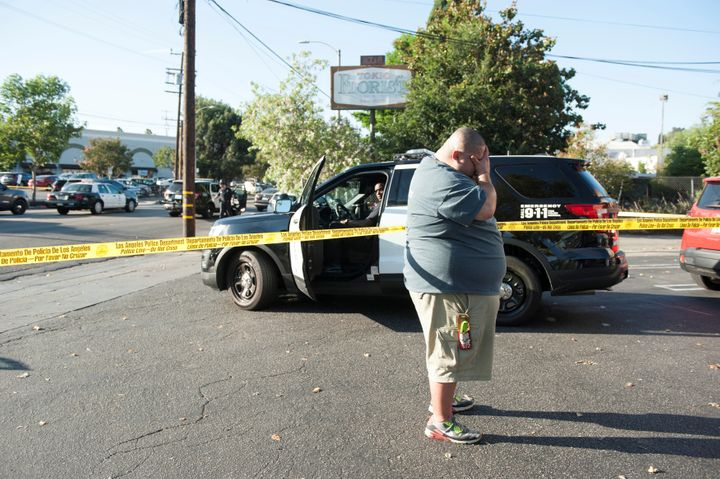 A Trader Joe's employee waits in a parking lot nearthe grocery store where a hostage situation unfolded in Los Angeles
