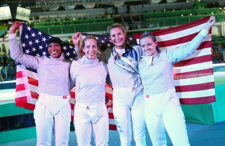 America's Ibtihaj Muhammad, Mariel Zagunis, Monica Aksamit, and Dagmara Wozniak (left to right) pose after their victory over Italy in the women's saber team bronze medal match at the 2016 Summer Olympic Games.