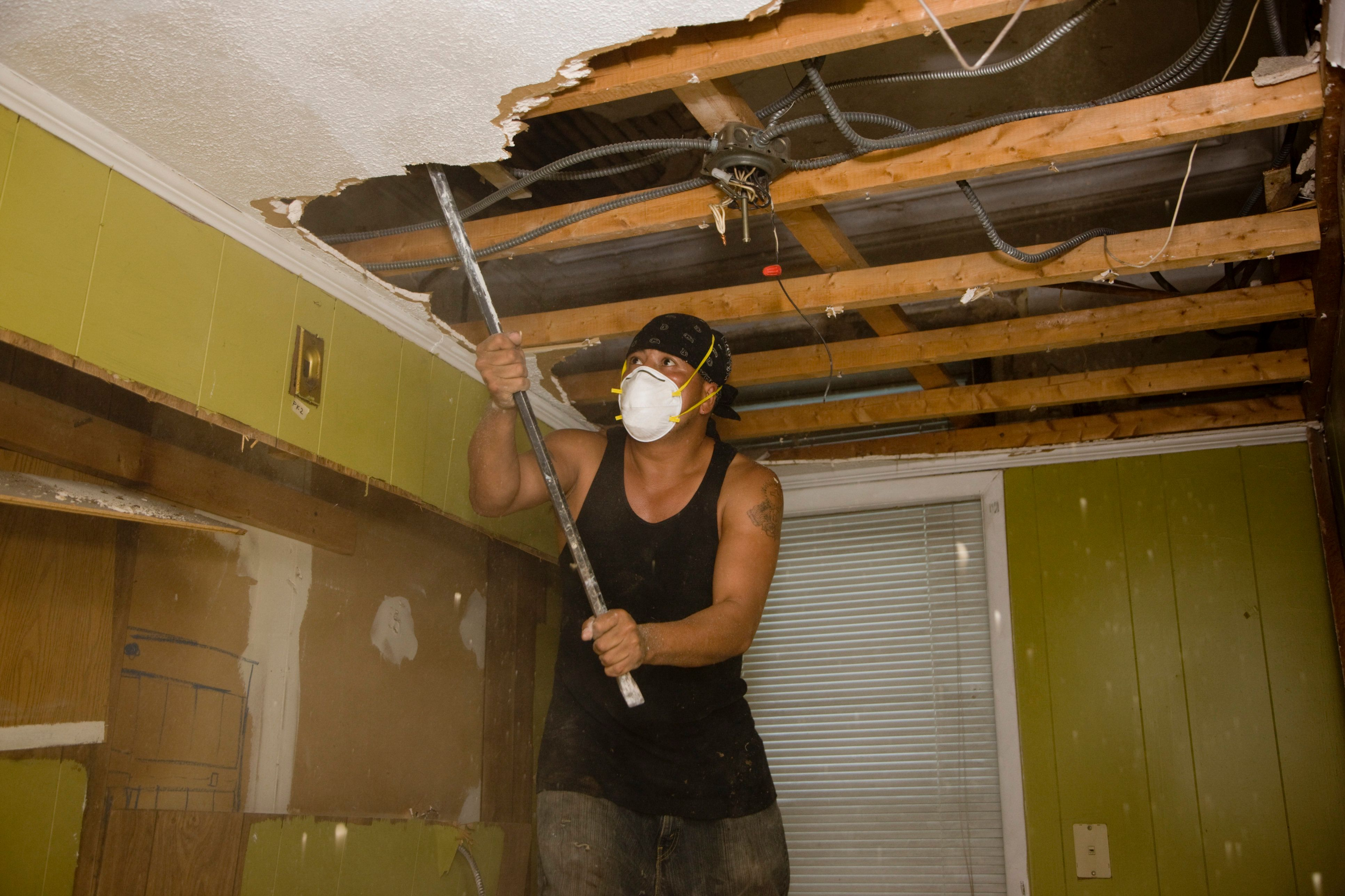 man removing ceiling in old house