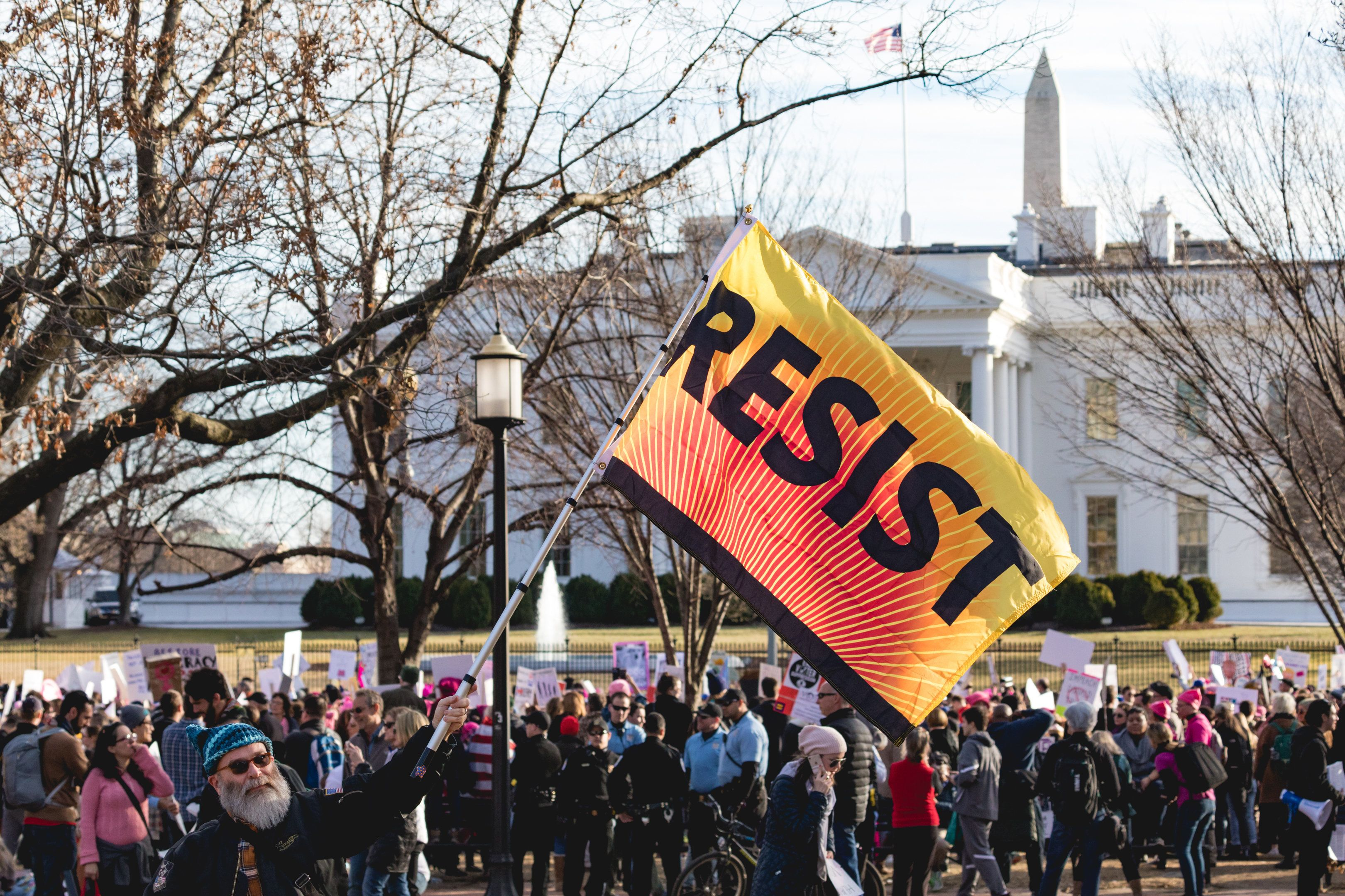 "Joseph Dress, from Washington, D.C., stands in Lafayette Square Park holding a resist flag up across the street from the White House, for the ""Women's March on Washington 2018"", on Saturday, January 20, 2018. (Photo by Cheriss May) (Photo by Cheriss May/NurPhoto via Getty Images)"