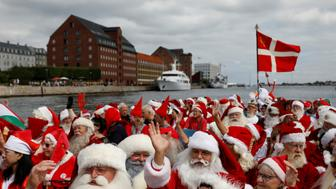People dressed as Santa Claus wave from a canal boat as they take part in the World Santa Claus Congress, an annual event held every summer in Copenhagen, Denmark, July 23, 2018.  REUTERS/Andrew Kelly