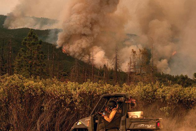 Firefighters drive along a fire break as the Ferguson fire burns in Stanislaus National Forest near Yosemite...