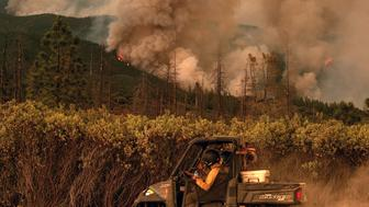 Firefighters drive along a fire break as the Ferguson fire burns in Stanislaus National Forest, near Yosemite National Park, California on July 21, 2018. - A fire that claimed the life of one firefighter and injured two others near California's Yosemite national park has almost doubled in size in three days, authorities said Friday. The US Department of Agriculture (USDA) said the so-called Ferguson fire had spread to an area of 22,892 acres (92.6 square kilometers), and is so far only 7 percent contained. (Photo by NOAH BERGER / AFP)        (Photo credit should read NOAH BERGER/AFP/Getty Images)