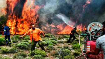 TOPSHOT - Firefighters and volunteers try to extinguish flames during a wildfire at the village of Kineta, near Athens, on July 24, 2018. - Raging wildfires killed 74 people including small children in Greece, devouring homes and forests as terrified residents fled to the sea to escape the flames, authorities said Tuesday. (Photo by Valerie GACHE / AFP) / The erroneous mention[s] appearing in the metadata of this photo by ANGELOS TZORTZINIS has been modified in AFP systems in the following manner: [-VALERIE GACHE--] instead of [--ANGELOS TZORTZINIS -]. Please immediately remove the erroneous mention[s] from all your online services and delete it (them) from your servers. If you have been authorized by AFP to distribute it (them) to third parties, please ensure that the same actions are carried out by them. Failure to promptly comply with these instructions will entail liability on your part for any continued or post notification usage. Therefore we thank you very much for all your attention and prompt action. We are sorry for the inconvenience this notification may cause and remain at your disposal for any further information you may require.        (Photo credit should read VALERIE GACHE/AFP/Getty Images)