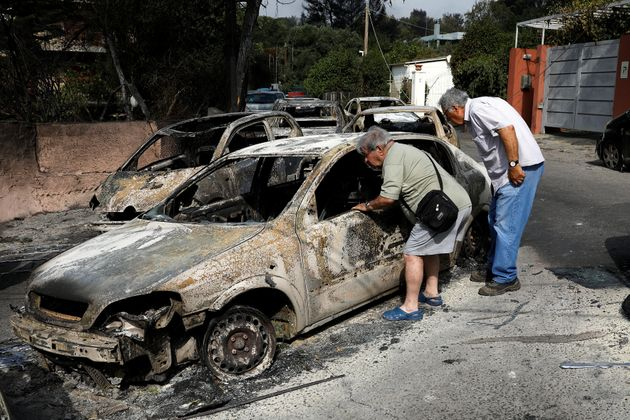 People look inside a burnt car following a wildfire at the village of Mati, near Athens,