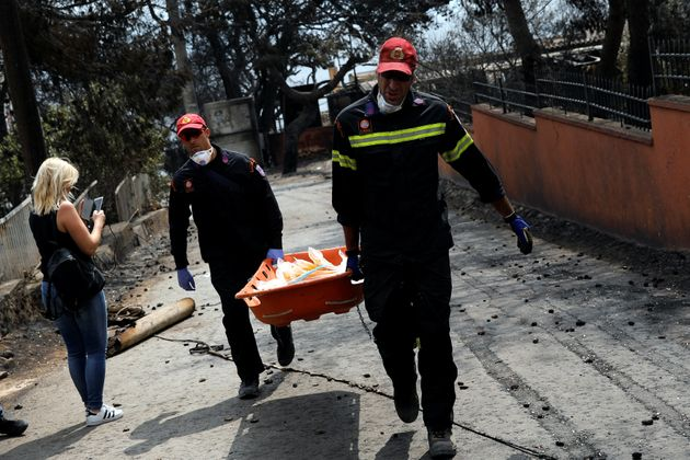 Firefighters carry a stretcher filled with body bags, following a wildfire at the village of Mati, near...