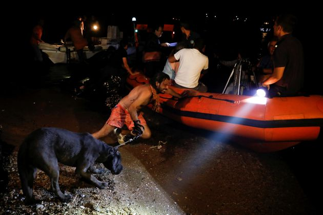 A man holding a dog pushes an inflatable boat as locals are evacuated during a wildfire at the village...