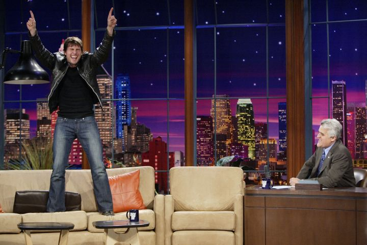 """Tom Cruise stands on a couch, something he likes to do, during an interview on """"The Tonight Show with Jay Leno"""" in 2005."""