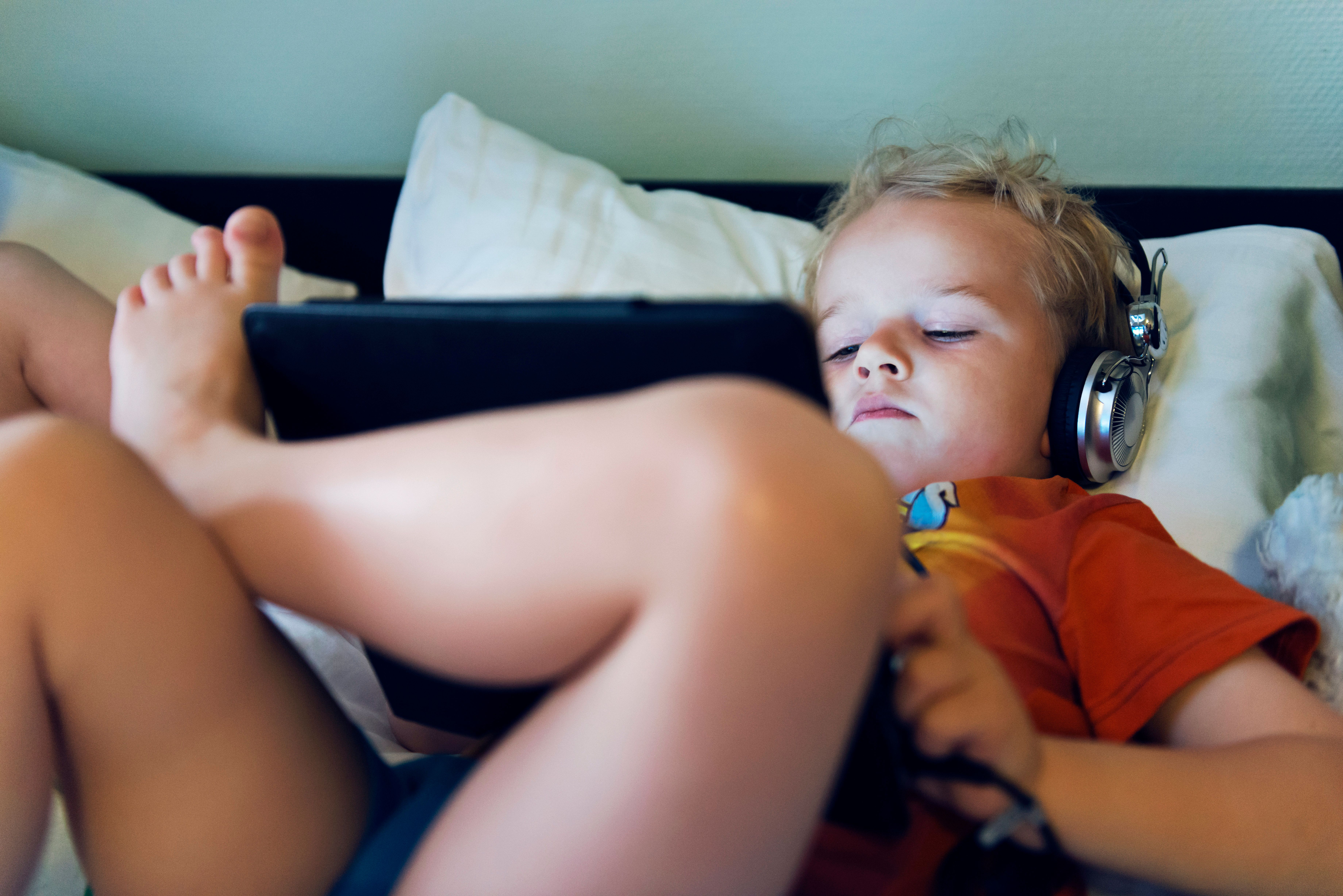 Boy wears headphones connected to a digital tablet while lying in bed. He looks at the content on the screen. It is night and he looks happy.  He could be streaming a movie, browsing the internet or playing a game.