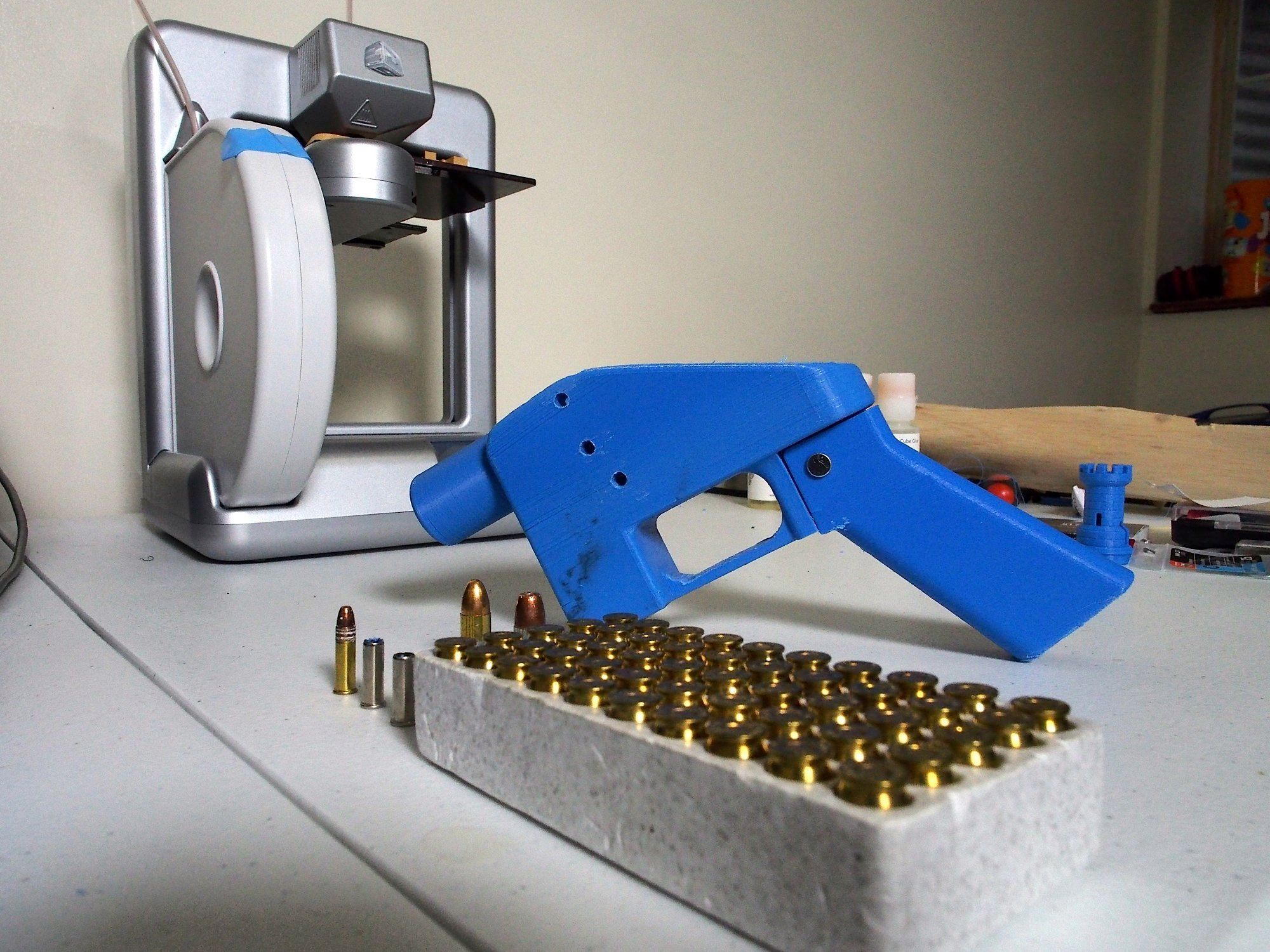 A Liberator pistol appears on July 11, 2013 next to the 3D printer on which its components were made. The single-shot handgun