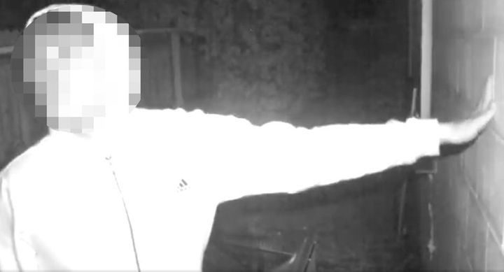 A still image from video of the suspect filmed outside the victim's residence. His face is blurred because police have arrest