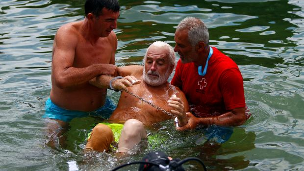 Bulgarian Yane Petkov, 64, is held after he wanted to set a new Guinness World Record by attempting to swim more than three kilometers at Macedonia's Lake Ohrid,Ê in a bag with his arms and legs tied up, in Ohrid, Macedonia July 24, 2018. ÊREUTERS/Ognen Teofilovski