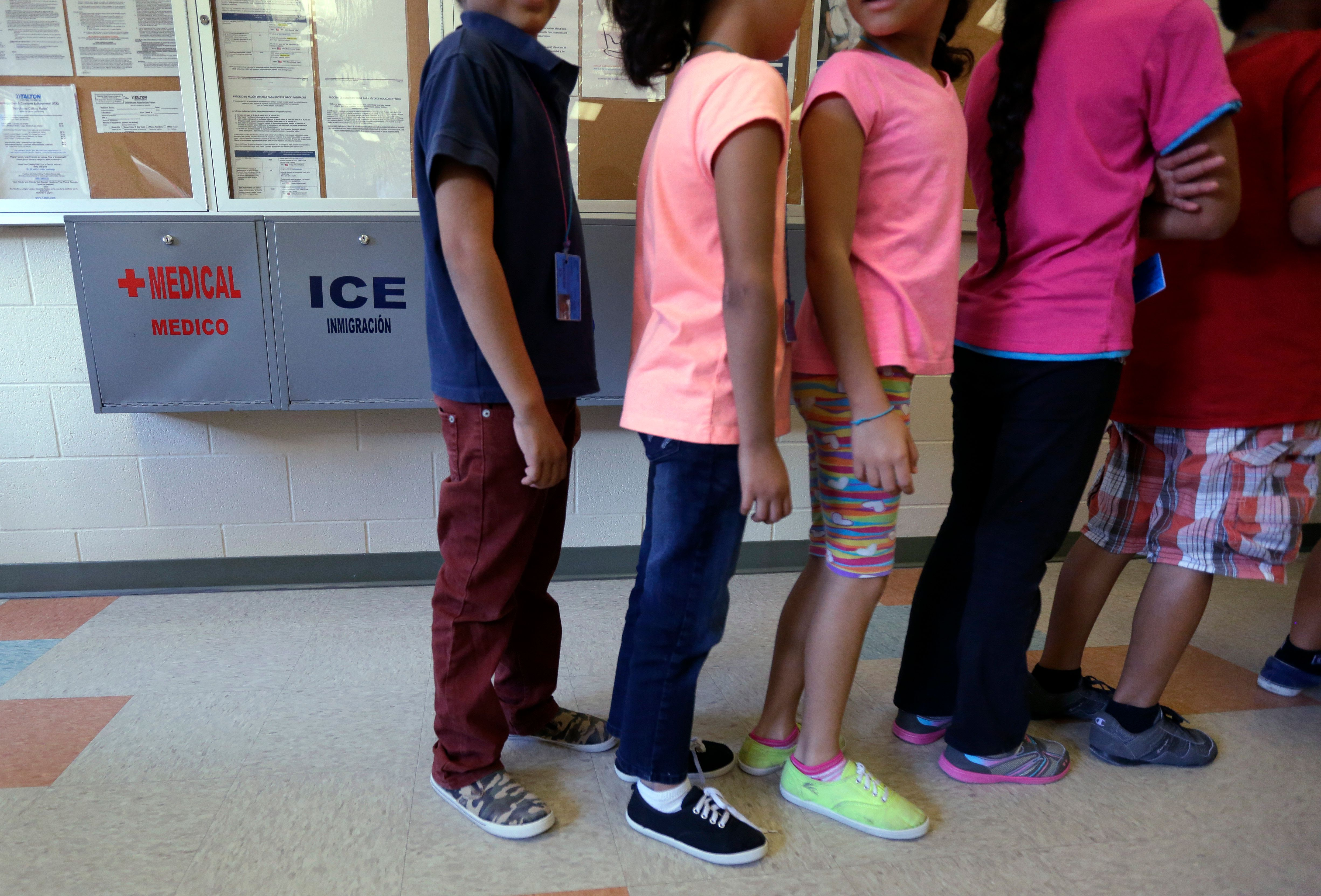 In this Sept. 10, 2014, file photo, detained immigrant children line up in the cafeteria at the Karnes County Residential Cen