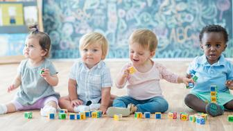 A group of multi-ethnic babies are indoors at a daycare. They are wearing casual clothing. They are sitting on the floor and playing with toy blocks.