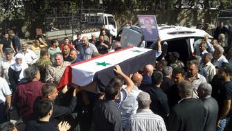 In this photo released by the Syrian official news agency SANA mourners carry a coffin of more than 200 people who were killed a day earlier by a series of suicide bombings launched by the Islamic States fighters on the eastern and northern countryside of the southern province of al-Sweida during a mass funerals in al-Sweida Syria Thursday July 26 2018 A Syrian government official says the death toll from coordinated Islamic State attacks on a usually peaceful city and its countryside has climbed to 216 in the worst violence to hit the area since the countrys conflict began
