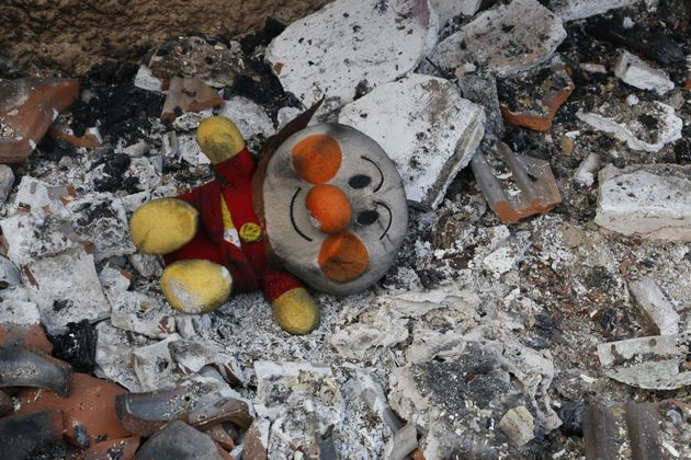 A charred doll is seen among ashes after a wildfire north of