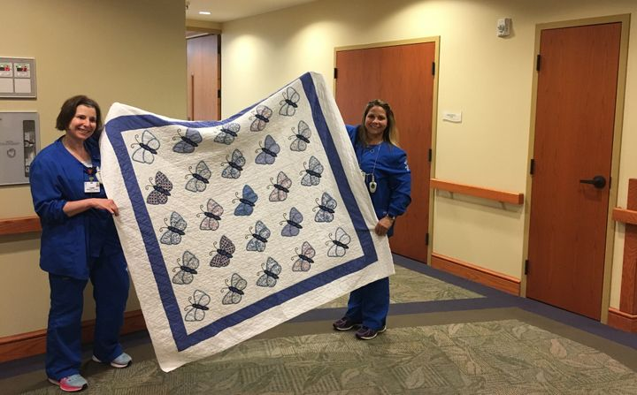 Tammy Wright, left, and Carrie Merk, hospice nursing assistants at the Medina Inpatient Hospice Care Center, hold up a quilt