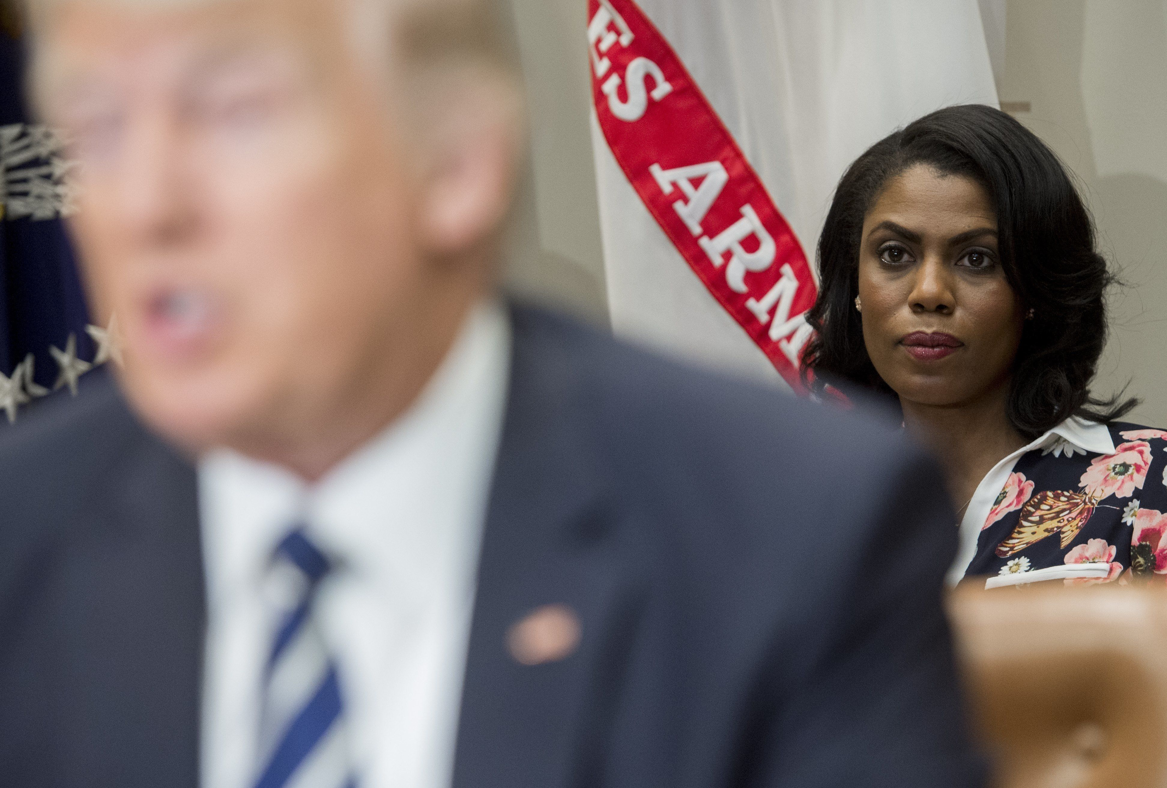 Omarosa Manigault (R), White House Director of Communications for the Office of Public Liaison, sits behind US President Donald Trump as he speaks during a meeting with teachers, school administrators and parents in the Roosevelt Room of the White House in Washington, DC, February 14, 2017. / AFP / SAUL LOEB        (Photo credit should read SAUL LOEB/AFP/Getty Images)