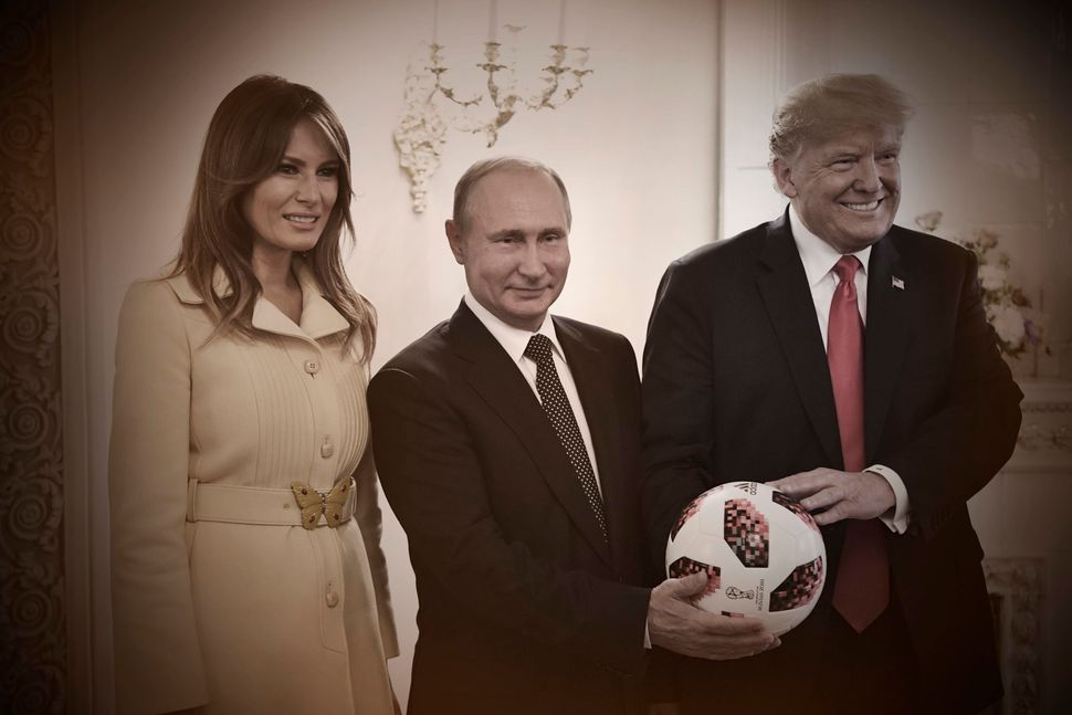 Russian President Vladimir Putin gives President Donald Trump a soccer ball from the World Cup as first lady Melania Trump jo